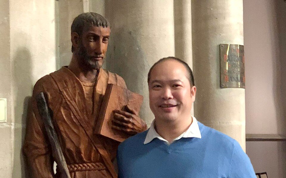 Fr Trung, Parish Priest, with statue of St Ignatius of Loyola in St Ignatius' Church.